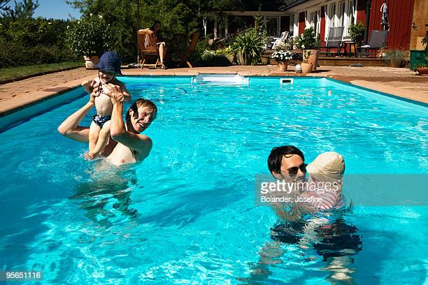 Two dads with one small children in a swimming pool, Sweden.