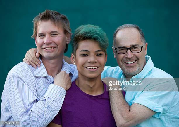 Two dads with transgender son portrait.