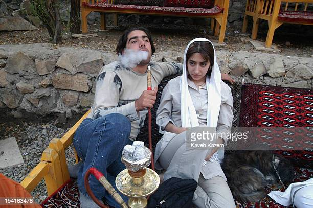 Two dating teenagers relax together as the young man puffs away on a waterpipe Zardband Iran October 2003 Iranians come to Zardband to relax on...