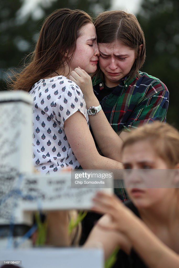 Two daughters of movie-theater-shooting-victim Gordon Cowden's embrace one another as another daughter leave messages on a cross at the makeshift memorial built across the street from the Century 16 theater July 23, 2012 in Aurora, Colorado. Two of Cowden's teenage daughters were with him in the theater when he was killed. Twenty-four-year-old James Holmes is suspected of killing 12 and injuring 58 others Friday during a shooting rampage at a screening of 'The Dark Knight Rises.'