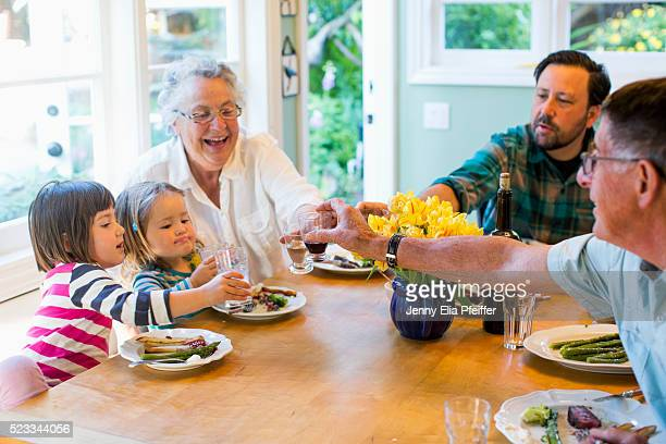 Two daughters (2-3), (4-5) with their family having dinner, California, USA