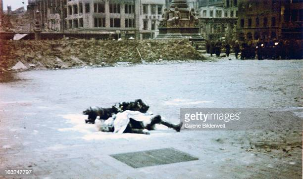 Two dead bodies are lying on the pavement at the Altmarkt near the Victory Monument February 1945 A group of people is standing in the background In...