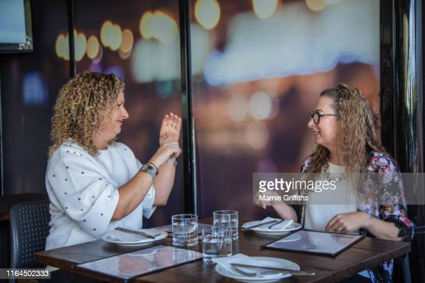 two deaf women having a signed conversation. - thisisaustralia stock pictures, royalty-free photos & images
