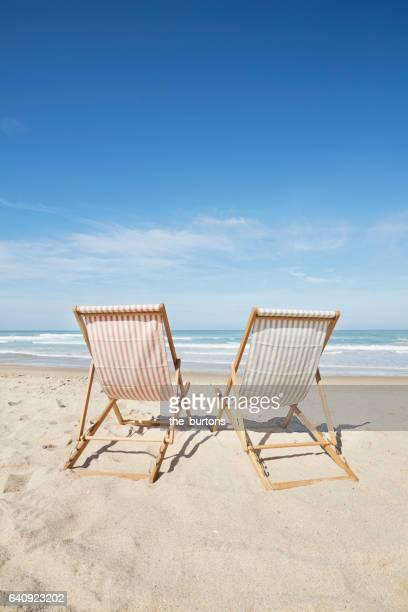 two deck chairs at beach - océan atlantique photos et images de collection