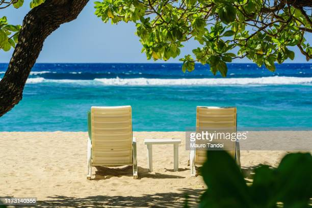 two deckchairs on the tropical beach of nusa dua - mauro tandoi stock pictures, royalty-free photos & images