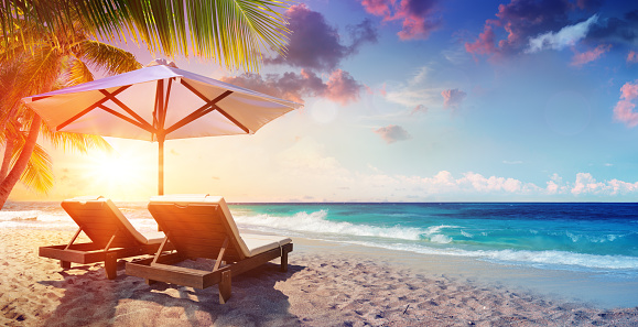 Two Deckchairs Under Parasol In Tropical Beach At Sunset 956989068