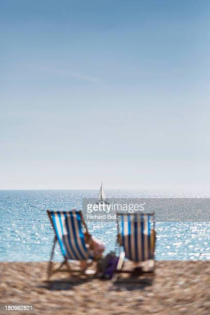 Two deckchairs with a yacht in the distance