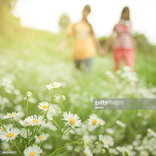 Two defocused girls in nature, focus is on foreground flowers.