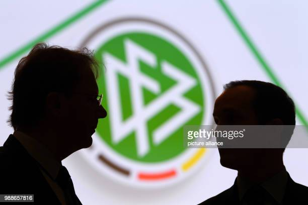 Two delegates speak in front of the DFB logo at the extraordinary federal conference of the German Football Association  in Frankfurt/Main Germany 8...