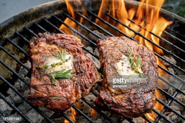 炎のグリルで2つのおいしい厚いジューシーなリブアイステーキ - ウシエビ ストックフォトと画像