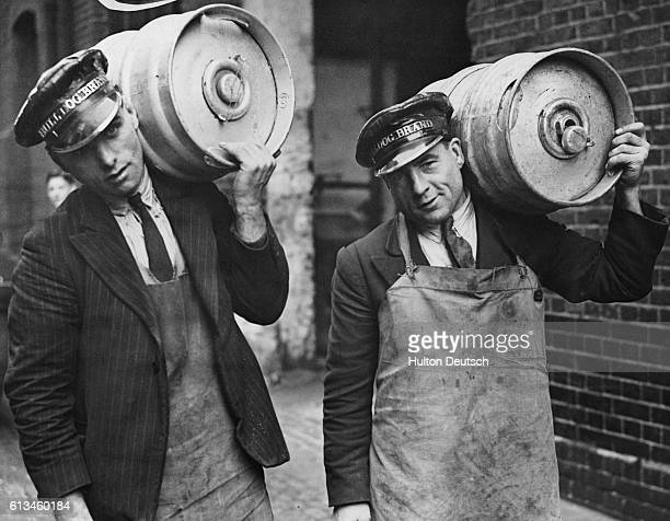Two delivery men carry nutbrown English ale in aluminium kegs King's Cross London