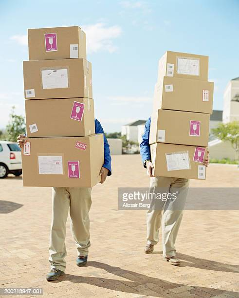 Two delivery men each carrying stack of boxes, obscuring faces