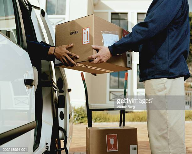 Two delivery men handing box to one another