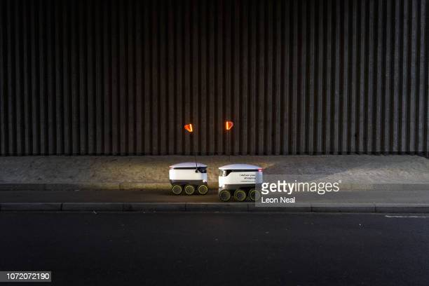 Two delivery robots pass on the pavement as they make home deliveries of groceries from the Coop food store on November 23 2018 in Milton Keynes...