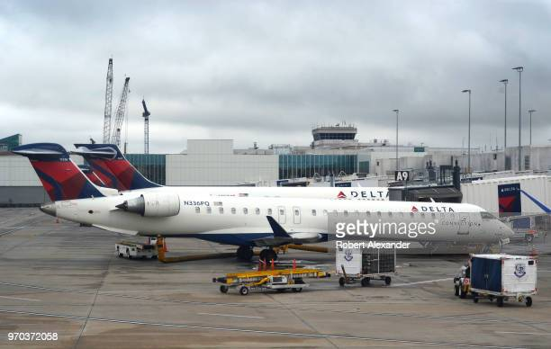 Two Delta Connection Bombardier CRJ900LR commercial jets are serviced at gates at Charlotte Douglas International Airport in Charlotte North Carolina