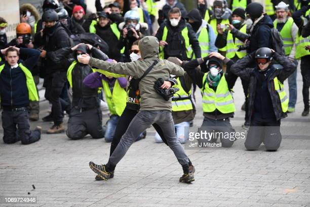 Two demonstrators dance in front a group kneeling and holding their hands on their heads as they take part in the demonstration of the yellow vests...