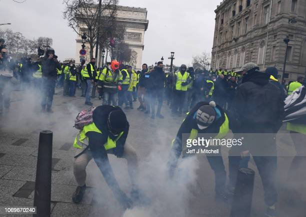 Two demonstrators grab tear gas canisters during the demonstration of the yellow vests near the ChampsElysees avenue on December 08 2018 in Paris...