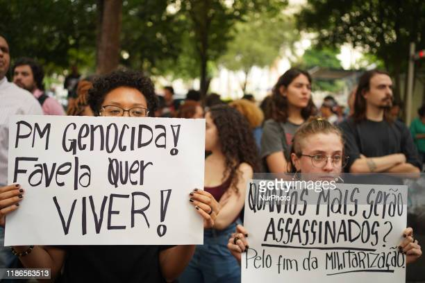 """Two demonstrators holding a signs that reads """"Genocidal Military Police! Favela wants to live! and How many more will be murdered? For the end..."""