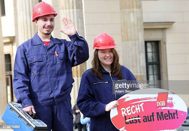 Two demonstrators posing as unequally paid constructions workers the woman holding a sign reading 'Not a Wish But a Right to More' demonstrate during...