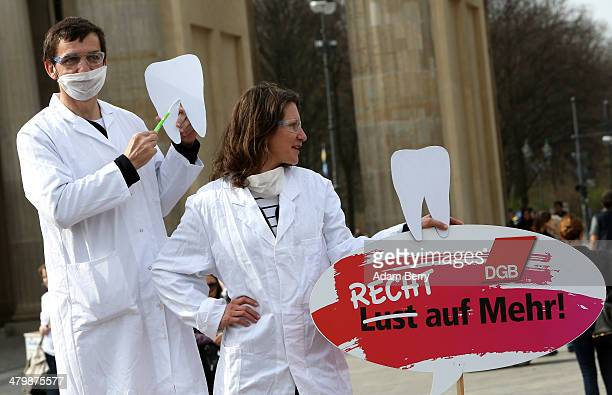 Two demonstrators posing as unequally paid dentists the woman holding a sign reading 'Not a Wish But a Right to More' demonstrate during the 'Equal...