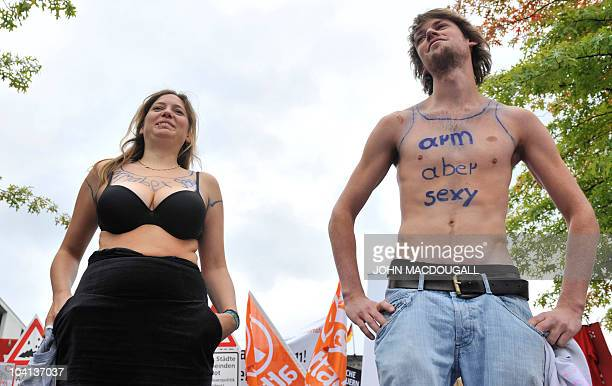 Two demonstrators pull off their tshirts to reveal a 'poor but sexy' slogan inscribed on their bodies during a mock fashion show in front of Berlin's...
