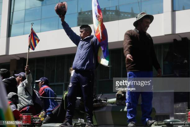 Two demonstrators stand with a flag of Whipala on a police tank during a funeral procession of the victims killed during clashes with police at the...