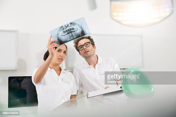 Two dentists in dental surgery discussing x-ray image
