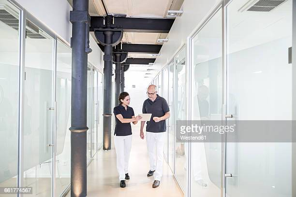 Two dentists using digital tablet in corridor