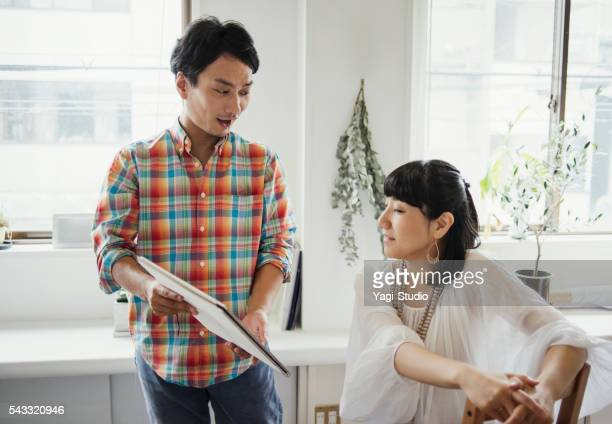 Two designers designers looking at a Fashion Drawing
