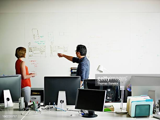 Two designers in office discussing project