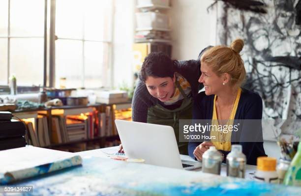 Two designers looking happily at the laptop