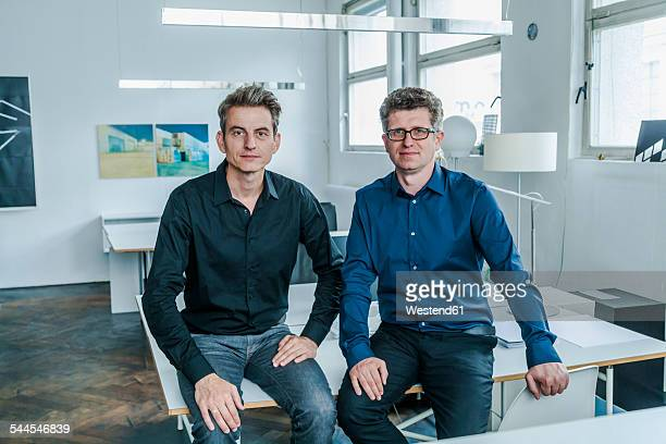 two designers sitting in their studio - côte à côte photos et images de collection
