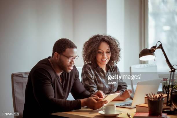 Zwei Designer mit einem digital-Tablette zusammen und Lächeln