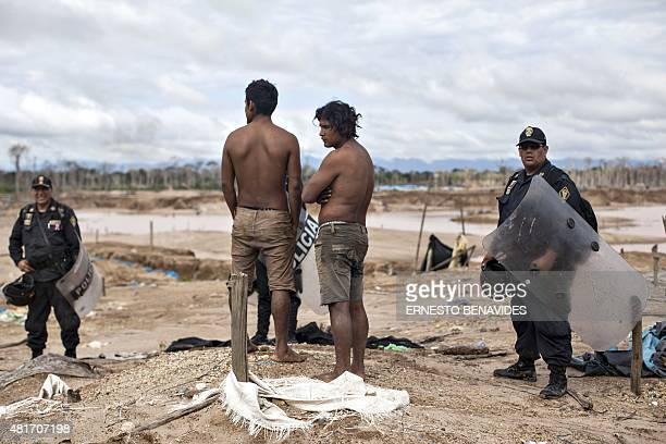 Two detained miners remain under custody during an interdiction operation in the illegal gold mining area of La Pampa in Madre de Dios southern...