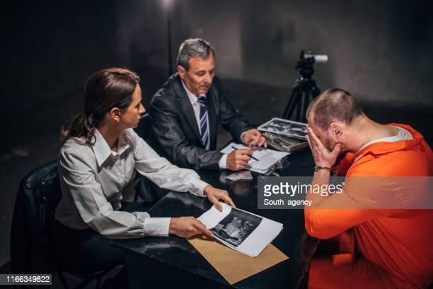 尋問室で2人の刑事と男性囚人 - 執行猶予 ストックフォトと画像