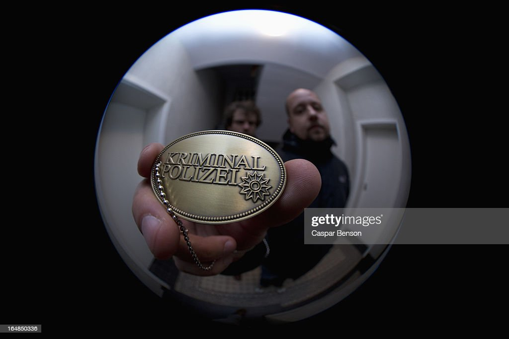 Two detectives showing a crime police (German: Kriminal Polizei) badge to a peephole : Stock Photo