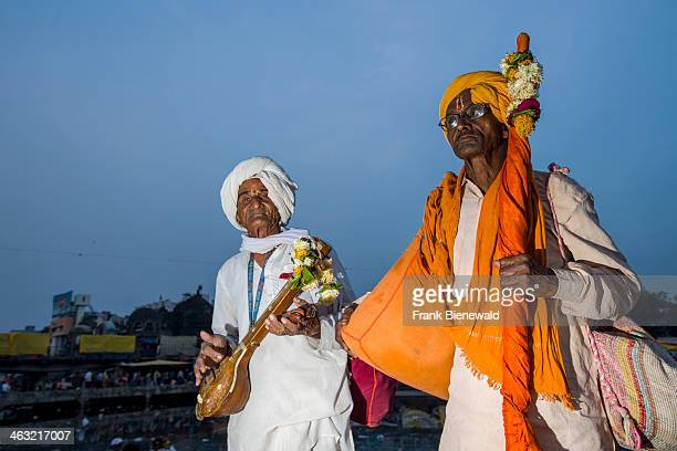 Two devotees with their music instruments are standing at the banks of the holy river Godwari