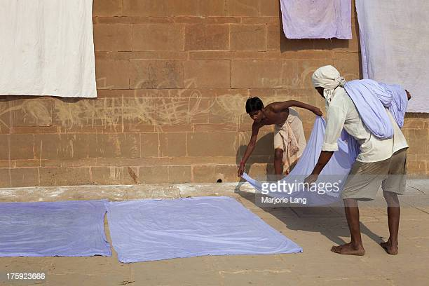 CONTENT] Two dhobi wallah workers are stretching out linen under the sun for drying on the ghats of Varanasi by the Ganges river in the morning Uttar...