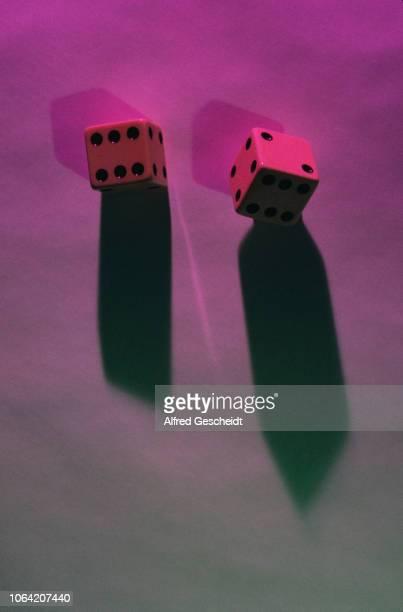 Two dice illuminated by a beam of fuchsia light US circa 1985