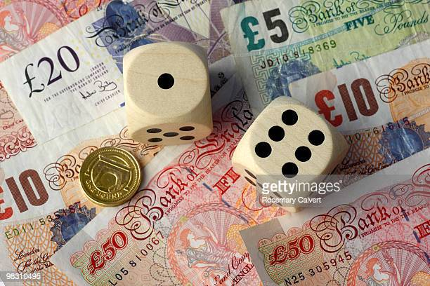 Two dice, one and six, pound coin and notes