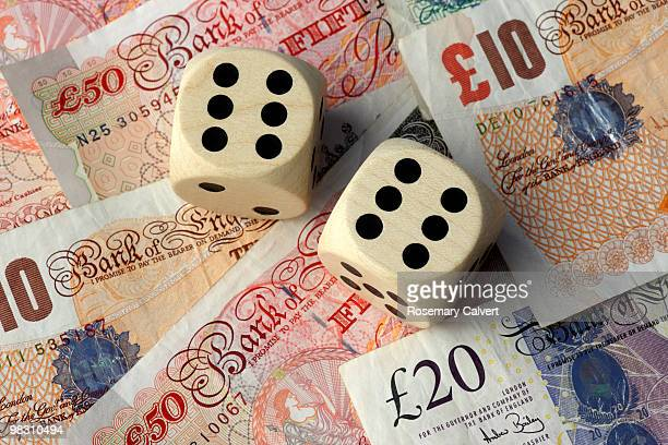 two dice, two sixes, background of pound notes. - fifty pound note stock pictures, royalty-free photos & images