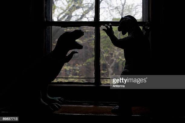 Two dinosaur figurines in silhouette in front of a window