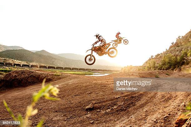 two dirt bike riders jumping during sunset. - stunt stock pictures, royalty-free photos & images