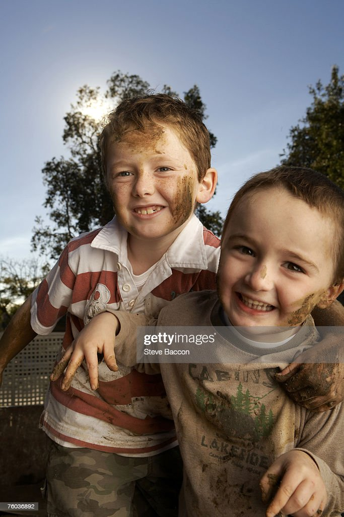 Two dirty boys (6-7, 8-9)  playing outdoors, portrait : Stock Photo