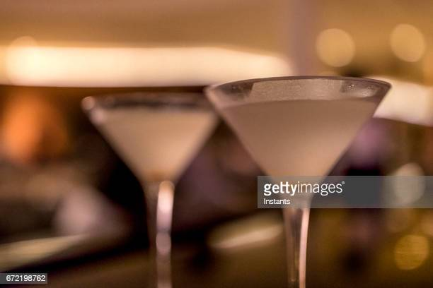 Two dirty martinis on a bar counter.