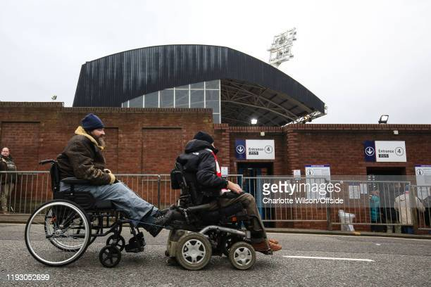 Two disabled Arsenal fans make their way to the match in their wheelchairs with one pulling the other ahead of the Premier League match between...