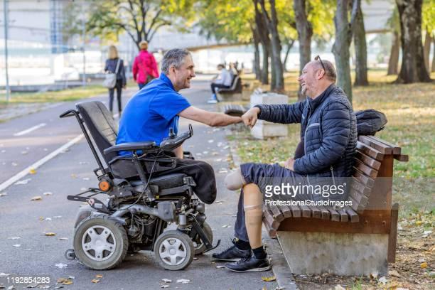 twee gehandicapte mannen in gesprek in het park - menselijke ledematen stockfoto's en -beelden