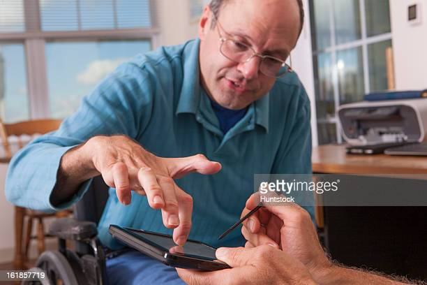 two disabled men sitting in wheelchairs and using a digital tablet, one with deformed hands - deformed hand stock pictures, royalty-free photos & images