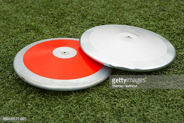 Two discuses on artificial turf