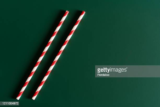 two disposable paper striped red-white tubules on a dark green emerald background - emerald green stock pictures, royalty-free photos & images